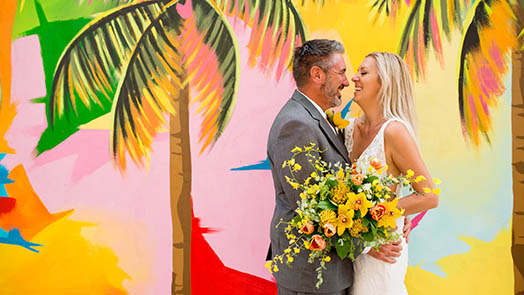 Wedding couple in front of colorful mural in St. Thomas US Virgin Islands.
