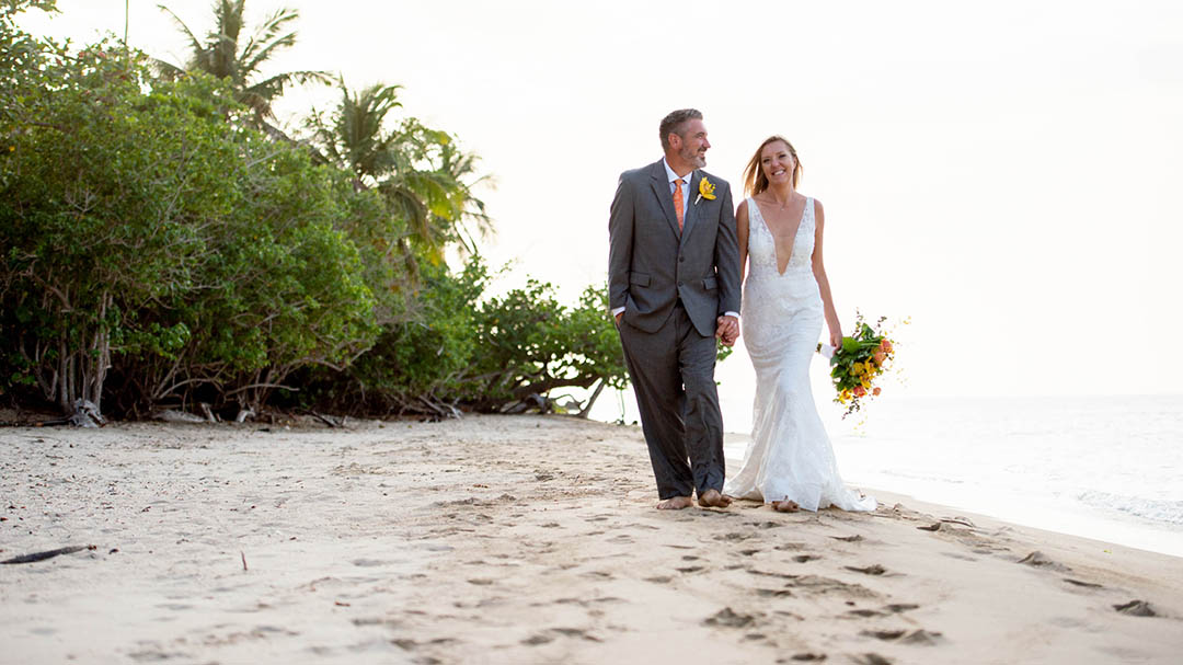 Married couple walking happily barefoot in the sand in St. Thomas.