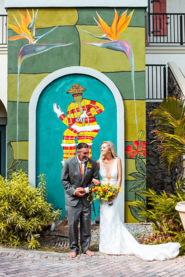 Happily married couple in front of a colorful mural in St. Thomas.