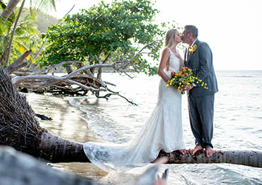 Loving couple kissing on a palm tree overhanging the water in St. Thomas USVI.