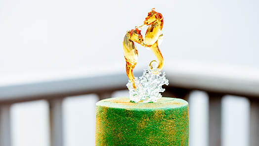Close-up of crystal seahorse wedding cake topper.